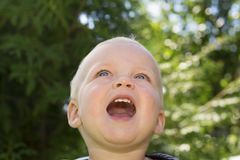 Close-up portrait of cute smiling one year toddler against green nature background. adorable baby boy looking up and Royalty Free Stock Photo
