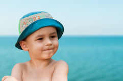 Close-up portrait of a cute, smiling young child at the beach. People, travel, holidays and tourism concept. Stock Photo