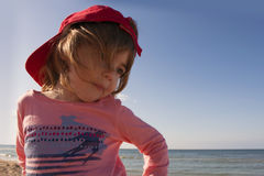 Close-up portrait of a cute, smiling young child at the beach in a red cap Royalty Free Stock Images