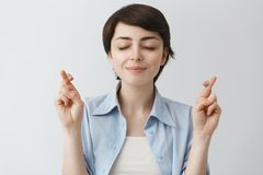 Close up portrait of cute student girl with stylish short haircut holding fingers crossed and eyes closed asking for. Luck in university exams Stock Photo