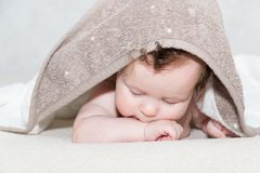 Close up portrait of cute three month old baby covered with a bath terry towel over her head lying on tummy in the Stock Images