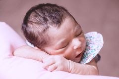 Cute two weeks old newborn baby girl sleeping peacefully. Close up portrait of a cute two weeks old newborn baby girl wearing a floral dress, sleeping peacefully Royalty Free Stock Photography