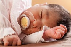 Cute two weeks old newborn baby girl with a pacifier. Close up portrait of a cute two weeks old newborn baby girl wearing soft pink knit clothes, sleeping Stock Photo