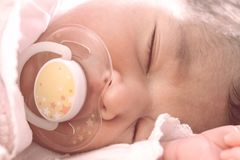 Cute two weeks old newborn baby girl with a pacifier. Close up portrait of a cute two weeks old newborn baby girl wearing soft pink knit clothes, sleeping Royalty Free Stock Photography