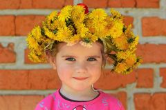 Close up portrait of a two years old girl wearing a dandelion wreath. Close up portrait of a cute two years old girl wearing a dandelion wreath Royalty Free Stock Images