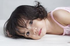 Cute Little Girl. Close up portrait of a cute, wide-eyed asian little girl lying down in bed royalty free stock photography
