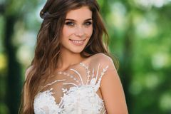 Close up portrait of cute young bride with long hairs dressed in beautiful white marriage dress. Pretty girl on greet. Trees background smileing at wedding day Royalty Free Stock Photography