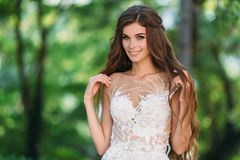 Close up portrait of cute young bride with long hairs dressed in beautiful white marriage dress. Pretty girl on greet. Trees background smileing at wedding day Stock Image