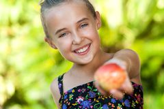 Cute healthy girl offering red apple. Close up portrait of cute young girl offering red apple outdoors Royalty Free Stock Photo