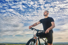 Close-up portrait of the cyclist against beautiful blue sky with clouds. Stock Images