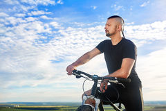 Close-up portrait of the cyclist against beautiful blue sky with clouds. Attractive sportsman in the black sportwear. Beautiful background. Travelling in the Stock Image