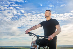 Close-up portrait of the cyclist against beautiful blue sky with clouds. Stock Photography