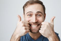 Close-up portrait of dark-haired bearded male customer with broad smile, demonstrating white teeth, looking at the. Close-up portrait of dark-haired bearded male Stock Photo