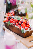 The close-up portrait of the delicious cake derorated with the strawberries and cherries located on the wooden board. royalty free stock photos