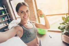 Close up portrait of delightful beautiful ideal slim sportive po. Werful muscular positive woman dressed in tight gray top demonstrating her biceps taking selfie Stock Photo