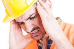 Close-up portrait of depressed constructor holding his head with. Hands as sorrow and migraine concept isolated on white background stock photography