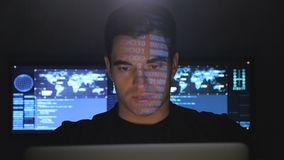 Portrait of developer programmer working on computer in a data center filled with monitor screens. Binary code on his. Close-up portrait of developer programmer stock footage