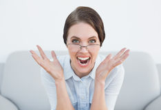 Close up portrait of a displeased woman screaming on sofa Royalty Free Stock Photos