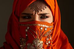 Studio shot of a young charming woman wearing the terracotta hijab decorated with sequins and jewelry. Arabic style. stock photography
