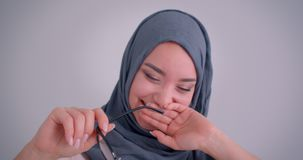 Close-up portrait of dreamy muslim businesswoman in hijab plays with her eyeglasses and laughing hardly. stock video footage