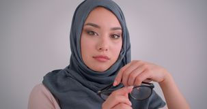 Close-up portrait of dreamy muslim businesswoman in hijab plays with her eyeglasses and watches calmly into camera. stock footage