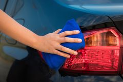 Close-up portrait of a driver woman cleaning her car with microf Royalty Free Stock Image