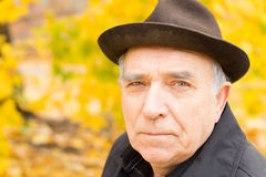 Close up portrait of an elderly man. Looking at the camera with a serious expression wearing a stylish hat while enjoying time outdoors in a colourful autumn royalty free stock photography