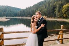 Close-up portrait of elegant beautiful wedding couple embracing near wooden fence on lake background. Elegant beautiful wedding couple embracing near wooden Royalty Free Stock Photo