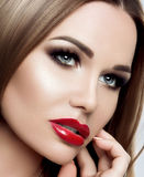 Close-up portrait of an elegant woman with bright makeup, red lips, long lashes, straight long hair, perfect eyebrows stock images