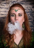 Close-up portrait of a elegant young redhead woman, with oriental make-up and shawl over her head bright red lips. Smokes a hookah, let the smoke out of his Royalty Free Stock Images