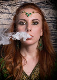 Close-up portrait of a elegant young redhead woman, with oriental make-up and shawl over her head bright red lips. Smokes a hookah, let the smoke out of his Stock Photography