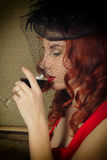 Close-up portrait of Elegant young redhead woman in a red dress, having a glass of red wine Stock Photo