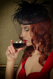 Close-up portrait of Elegant young redhead woman in a red dress, having a glass of red wine Stock Photos