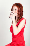 Close-up portrait of Elegant young redhead woman in a red dress, having a glass of red wine Royalty Free Stock Photos