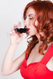 Close-up portrait of Elegant young redhead woman in a red dress, having a glass of red wine Royalty Free Stock Image