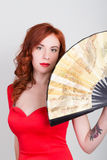 Close-up portrait of Elegant young redhead woman in a red dress with a large fan Stock Photos