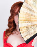 Close-up portrait of Elegant young redhead woman in a red dress with a large fan.  Stock Images
