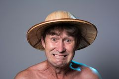 Close-up portrait of an embittered man with a naked torso in a hat Stock Image