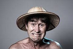 Close-up portrait of an embittered man with a naked torso in a hat Royalty Free Stock Photography