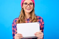 Close up portrait of excited cheerful satisfied teen girl wearing casual checkered shirt pink hat nerd eyewear hugging white with stock images