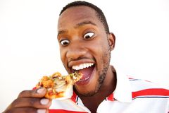 Excited young african man eating pizza Royalty Free Stock Photography