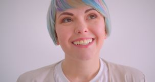 Close-up portrait of extraordinary caucasian girl with multicolored hair smiles happily into camera on white background. Close-up portrait of extraordinary stock video