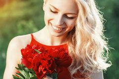 Close-up portrait of fashion beautiful smiling woman with red fl. Owers Stock Photo