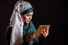Close up portrait of fashion Muslim female looking at the screen of tablet stock photos