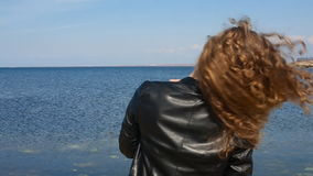 Close up portrait of fashion trendy woman running hand through curly hair blowing in wind by sea on beach. Happy female. Close up portrait of fashion trendy stock video footage