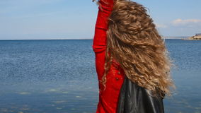 Close up portrait of fashion trendy woman running hand through curly hair blowing in wind by sea on beach. Happy female. Close up portrait of fashion trendy stock video