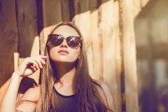 Close up portrait fashion woman in sunglasses. Trendy girl in summer. Wooden wall background Copy Space Royalty Free Stock Image