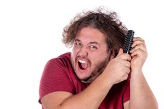 Close up portrait of fat man tries to comb his tangled and naughty hair with a small black comb isolated on white background. Close up portrait of fat man tries stock photography