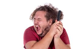 Close up portrait of fat man tries to comb his tangled and naughty hair with a small black comb isolated on white background. Close up portrait of fat man tries royalty free stock image