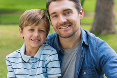 Close-up portrait of father and boy at park. Close-up portrait of a father and young boy sitting at the park royalty free stock photos